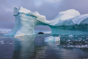 A zodiac full of tourist viewed through an arch in a large iceberg, Antarctica
