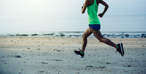 sporty young fitness woman running on beach