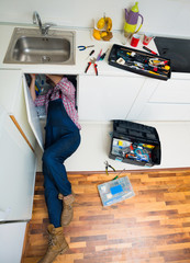 Adult Man Lying On Floor Repairing Sink In Kitchen