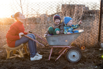 Happy little blond boy and his cute brother sitting in garden wheelbarrow on sunset background. Children are happy with mother of peasant woman. Warm spring day is good time to take walk