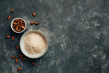 Bowl of almond flour and bowl of almonds from top view, copy space.