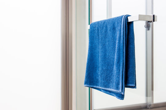 Blue towel prepared to use in the bathroom close up.