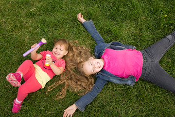 A portrait of two sisters on green grass, park outdoor - top view