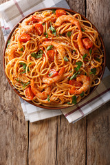 Spicy spaghetti with shrimps in tomato sauce close-up. Vertical top view from above
