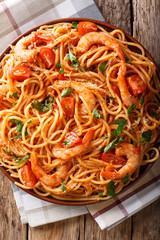 Portion of spaghetti with shrimps, parmesan cheese with tomato sauce close-up on a plate. Vertical top view