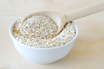 Oat bran in bowl with spoon on wooden background