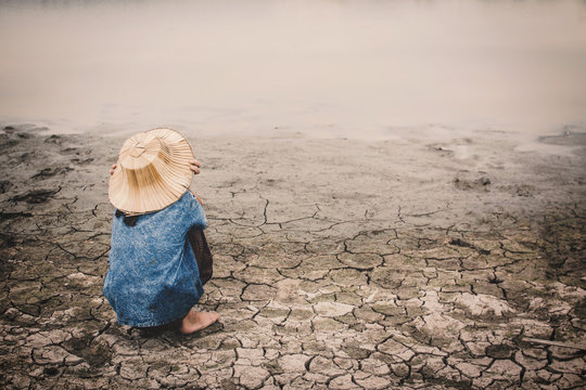 Sad girl and exhausted on cracked dry ground, Concept drought and shortage of water crisis