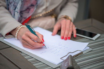 Close-up of female hands. Woman writing something sitting at cafe. Signing documents.