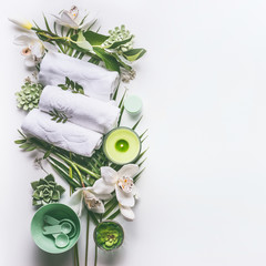 Green spa or wellness background with towels, candle, tropical leaves , orchid flowers, succulents and body and face care tools and accessories on white desktop, top view with copy space.