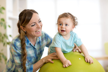 Happy mother and baby toddler on fitness ball in nursery at home. Gimnastics for kids on fitball.