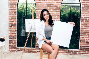 Young woman artist posing with empty canvas at home