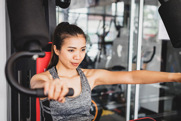 Young asian women with exercise-machine in sport gym