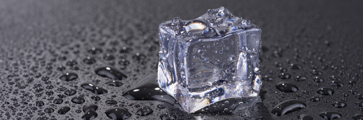 Single ice cube with water drops isolated on black background