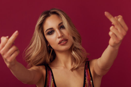Gorgeous blonde woman portrait giving middle fingers