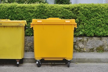 yellow plastic garbage can in the street