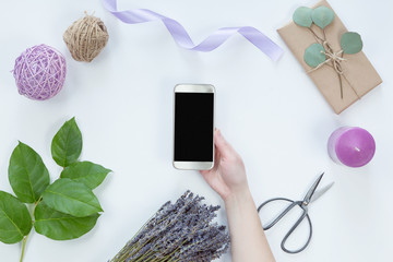 Top view of women hands working on cell phone on background with flowers, free text space, flat lay on white. Mobile phone with black screen copy space