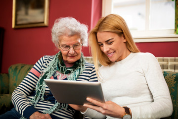 Two generation using tablet and smiling together