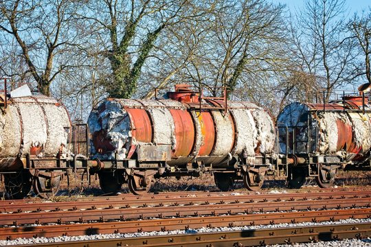 Degraded wagons with asbestos insulation on the side track of a local railway station waiting to be recycled.