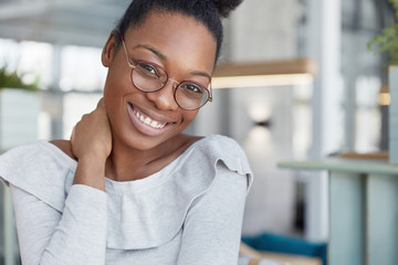Pleased attractive dark skinned female model wears glasses, has shining smile, glad to finish work and has break, poses against office interior. Glad African American woman with happy expression