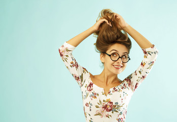 Funny pretty young woman in round glasses holding her hair up