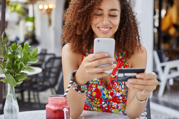 Cropped shot of beautiful African American woman with happy look, holds modern cell phone and credit card, makes shopping online, drinks smoothie in outdoor cafeteria. People and payment concept