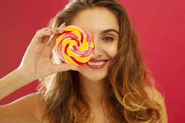 Portrait of a happy girl holding sweet candy over red background