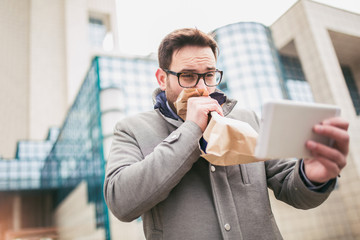 Businessman holding paper bag over mouth as if having a panic attack and looking in digital tablet.