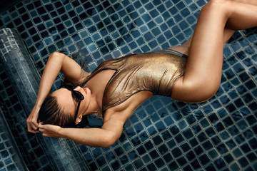 Girl in a gold swimsuit relaxes in the pool during a vacation