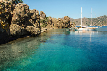 Tourist boats moored in blue lagoon at Camellia island in Aegean sea old olive tree near Marmaris Turkey journey trip holiday summer