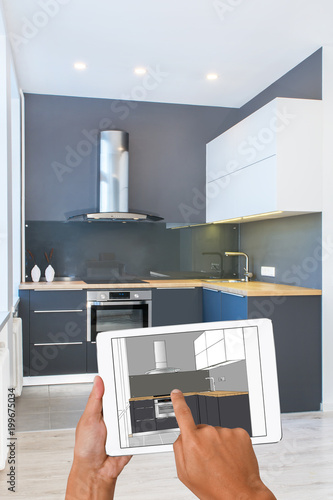 Business Hands Holding Tablet With Modern Kitchen Interior Sketch. In The  Background Real Finished Kitchen