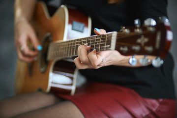 young girl in a red leather miniskirt and black pantyhose playing the guitar, close-up, shallow depth of field.