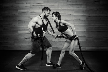 Muscular man with tattoos and beard and attractive girl pulling a rope in a black tank top and black shorts in the gym. Sportive couple doing crossfit exercise. Black and white portrait.