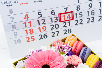 Valentines Day card. Box with beautiful colorful flowers and macaroons, February 14 mark on the calendar on light wooden background