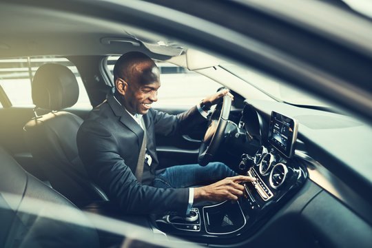 African businessman listening to music while driving through the