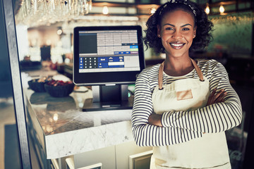 Smiling African waitress standing at the counter of a restaurant
