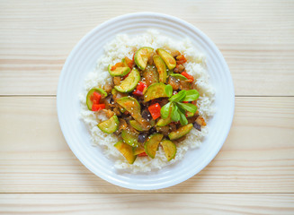A plate of rice with vegetables on wooden background. Asian cuisine.