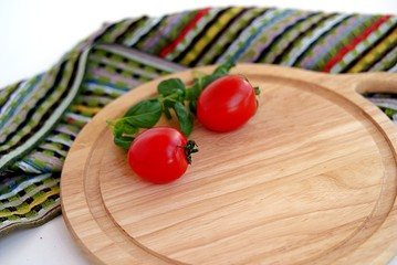 Ripe tomatoes and basil on a wooden board