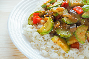 Rice with vegetables (zucchini, eggplant, onion, pepper) on wooden background. Asian cuisine.