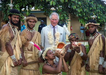 Britain's Prince Charles poses for a photograph with dancers during a visit to Port Vila Central Hospital, as he visits the South Pacific island of Vanuatu