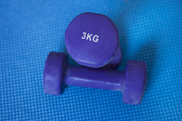 Neoprene coated iron dumbbells, a pair of 3 kg, used for muscle toning, aerobic and weight training, positioned on a blue mat, part of fitness classes and at-home workout routine