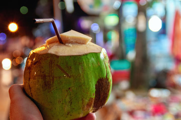 Opened green young coconut with tube for cocktail on the background of the lights night market. Exotic drink, healthy coconut milk