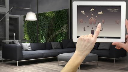 Smart remote home control system on a digital tablet. Device with app icons. Interior of minimalist living room in the background, architecture design.