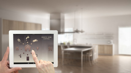 Smart remote home control system on a digital tablet. Device with app icons. Blurry interior of minimalist kitchen in the background, architecture design