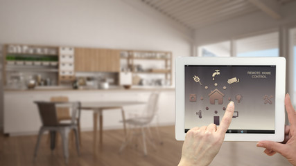 Smart remote home control system on a digital tablet. Device with app icons. Blurry interior of white kitchen in the background, architecture design