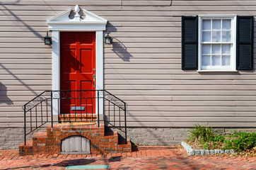 American Colonial House along a Brick Sidewalk with a Red Wooden Front Door and a White Window with Black Shutters. Alexandria, VA