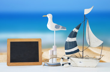 nautical concept with white decorative seagull bird, blackboard and boat over tropical sea landscape background.