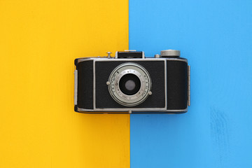Top view image of vintage photo camera over double colorful background.