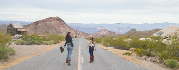 Women walking the center line of an abandoned highway