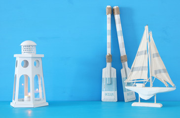 nautical concept with white decorative lighthouse lantern, wooden oars and boat over blue background.