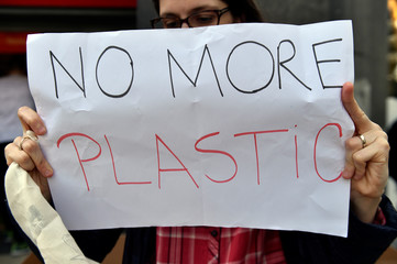 """An activist holds a placard as she takes part in the """"Plastic Attack"""" operation in an AD Delhaize store in Brussels"""